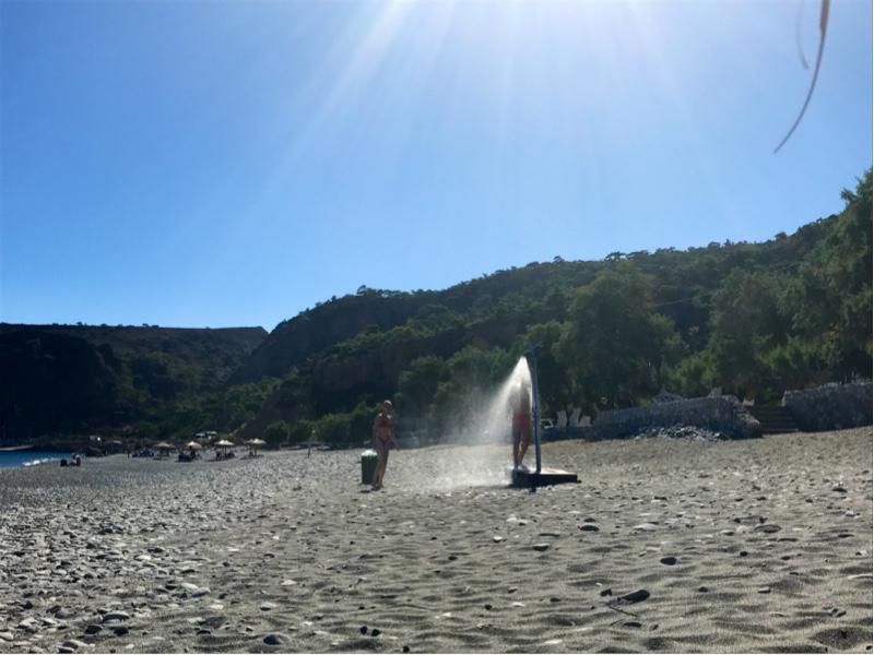 En person som dusjer på en strand.