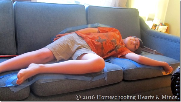 Peter in a tape body outline for Emma's detective mystery at Homeschooling Hearts & Minds