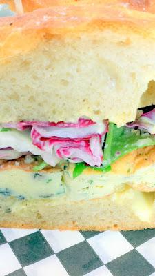 Marmo Deli & Bar Frittata Sandwich with five herb frittata, housemade foccacia, arugula, radicchio, endive, lemon vin, aioli, pecorino