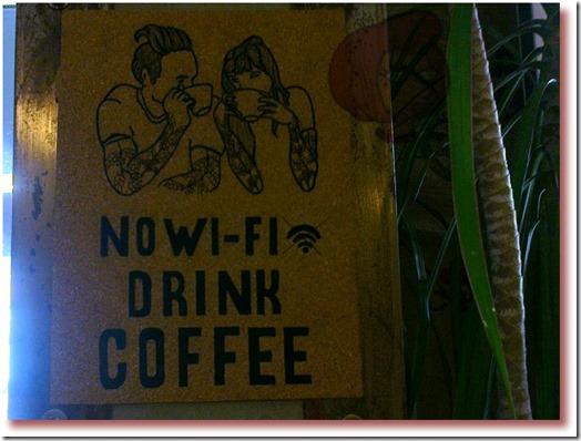 Foto de desenho de um casal bebendo café com uma frase informando que no Fábrica - Coffee Roasters de Lisboa não há wi-fi disponível
