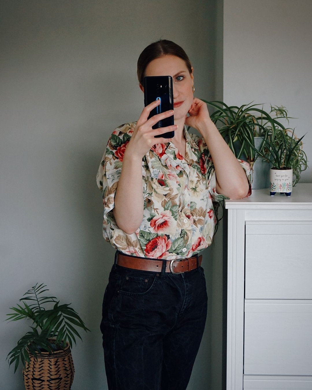 Amy is wearing a vintage floral shirt tucked into black high waisted jeans
