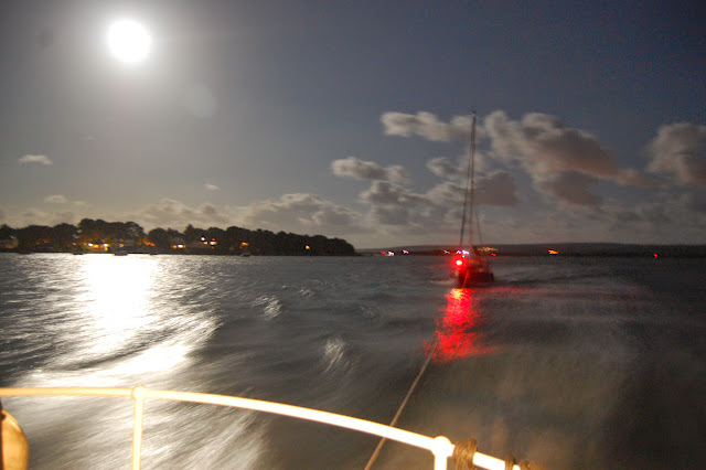 Poole all-weather lifeboat towing the yacht inside Poole Harbour under the light from a supermoon - the full moon that's closest to Earth over the year so looks bigger and brighter than at other times of the year. 10 August 2014 Photo: RNLI Poole/Dave Riley
