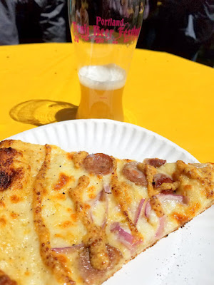 HOT LIPS Pizza's Beer Bratlips, a pizza with Smoked Carlton Farms bratwurst with Tillamook extra-sharp cheddar, fresh onions, mozzarella, and a garlic parmesan base finished with whole grain maple mustard glaze