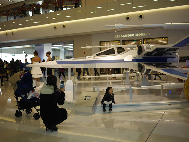 little girl posing for photo in front of a Star Wars X-wing fighter at the IAPM shopping center in Shanghai