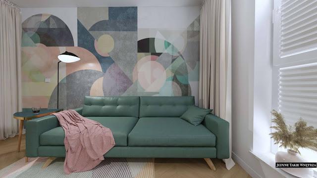 Zielona kanapa na nóżkach, w tle pastelowa, geometryczna tapeta.