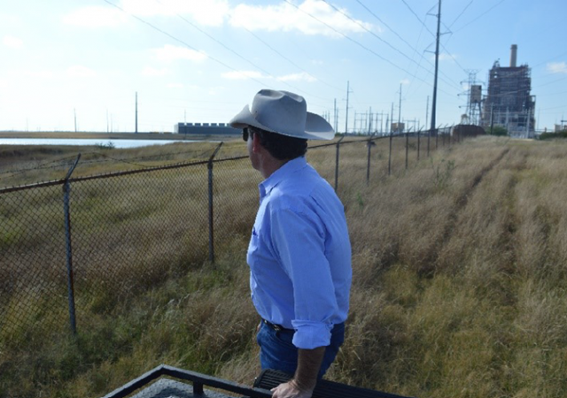 "South Texas Rancher Alonzo Peeler Jr. stands near land where all the vegetation has died, he believes because of contaminants leaking out of a coal ash waste pond behind this fence. ""The toxic pollution leaking from these coal ash dumps is threatening our family's ranch and our heritage,"" said Jason Peeler, who helps run the Peeler Ranch. ""We've asked the power company to stop polluting our land and clean up the mess. But their response has been to threaten to seize our land through eminent domain instead of cleaning it up. It's outrageous — and an example of how coal ash pollution can cause real damage."" Photo: Ari Phillips / Environmental Integrity Project"