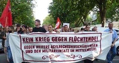 Demonstrierende mit Fahnen und Transparent: »Kein Krieg gegen Flüchtende! Gegen weitere Asyrechtsverschärfungen und den Militäreinsatz im Mittelmeer!«