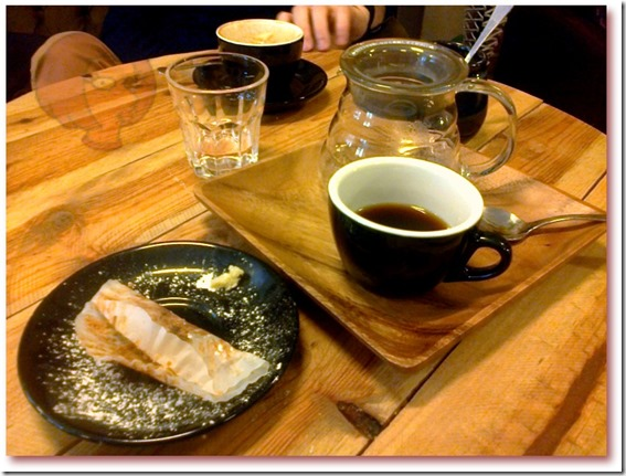 Foto de uma das mesas redondas da Coffee Shop, com xícaras, açucareiro com açúcar mascavo, mini bule, copo e um prato de sobremesa com o que sobrou de um muffin