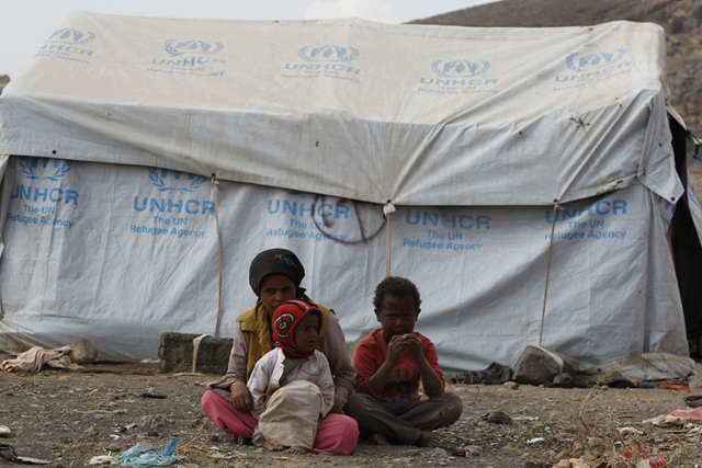 Around 200 displaced families live in an informal settlement in Dharwan, Yemen. Here, a 12-year old girl keeps watch over her younger brothers. Photo: Mohammed Hamoud / UNHCR