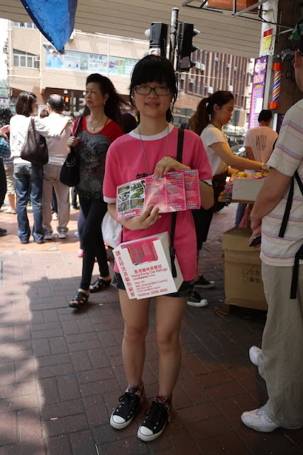 female middle school student in Hong Kong with flyers and a donation box