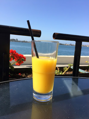 Glass med appelsinjuice med sjøen i bakgrunnen.