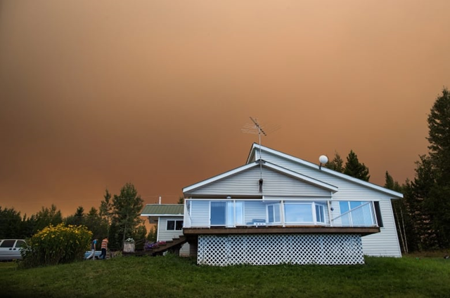 Two boys walk outside their home on a ranch as the Shovel Lake wildfire burns in the distance sending a massive cloud of smoke into the air near Fort St. James, B.C., on Friday, 17 August 2018. Photo: Darryl Dyck / Canadian Press