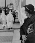 "Klu Klux Klan - Montgomery 1956 A woman watches as robed Ku Klux Klansmen walk in downtown Montgomery, prior to a cross-burning rally that night, November 24, 1956. Circulars advertising the Klan meeting said, ""We believe in white supremacy. We need you—you need us."" (AP/Wide World Photos)"
