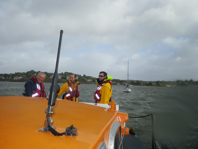 RNLI volunteer crew members aboard the ALB, with the yacht under tow in the background - 27 October 2013. Photo credit: RNLI Poole