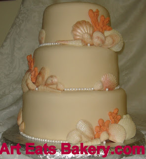 Cream color fondant wedding cake with sugar pearls, white chocolate seahells and coral.