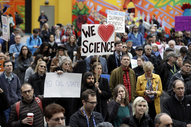 People hold signs as they listen to a group of scientists speak during a rally in conjunction with the American Geophysical Union's fall meeting in San Francisco, 13 December 2016. Photo: Marcio Jose Sanchez / AP