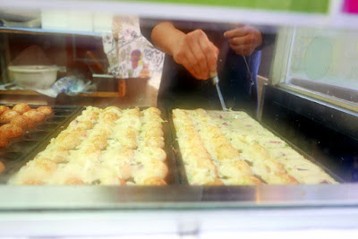 Sights of Osaka - Amerikamura - while waiting in line for takoyaki you can watch them being made fresh. First you pour in a batter into special takoyaki pans, and then add the seasoning and the little bits of octopus. Then you turn them over to cook the other side, and when the balls are fully formed, expertly place them 2 at a time into containers before adding the sauces and whatever are the famous toppings of that takoyaki stand