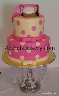 Girl's two tier pink and yellow fondant polka dot, ribbon and bows baby shower cake design with baby bottom topper