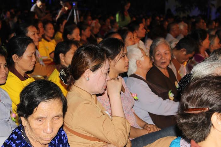 Một phụ nữ trung niên gạt nước mắt khi sư thầy giảng về đạo làm con