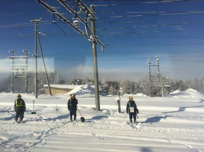 線路の雪をかく人々