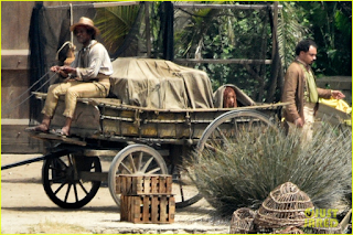 Halle Bailey as Ariel hiding in the back of a wagon