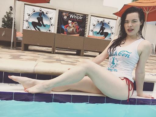 Jasmin Jai in red string bikini bottoms and Fetcon tank sitting next to the pool