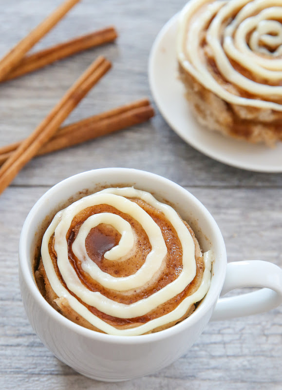 overhead photo of a Cinnamon Roll Mug Cake with cinnamon sticks in the background