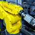 A FANUC robotic arm loads blanks for machining aerospace fasteners into a Tsugami opposed gang tool lathe customized for automation by IMG.