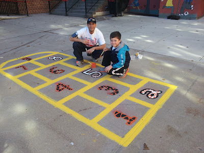 Mr. Weinman and his son, Nicholas, painting one of the hopscotch courts at PS41.