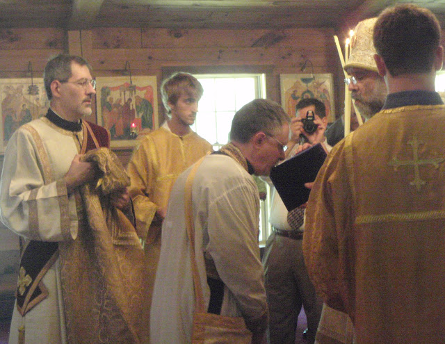 Fr. John is invested with the purple kamilavka, and venerates it.