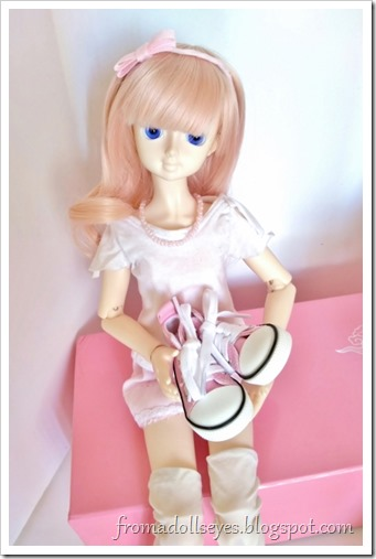 A msd sized bjd with strawberry blond hair (Usagi) holding her new pink sneakers.