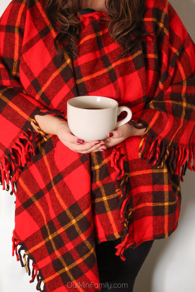 woman in buffalo plaid shawl holding bowl of soup
