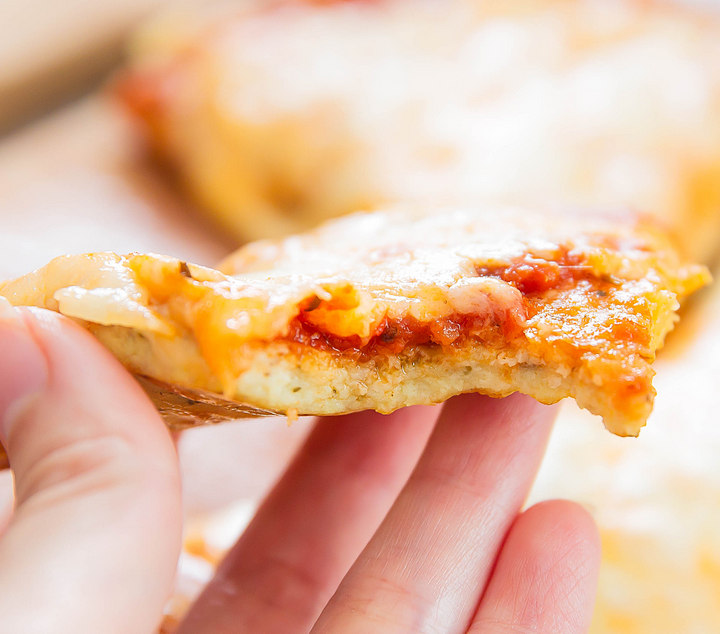 a close up of a slice of pizza with a bite taken out