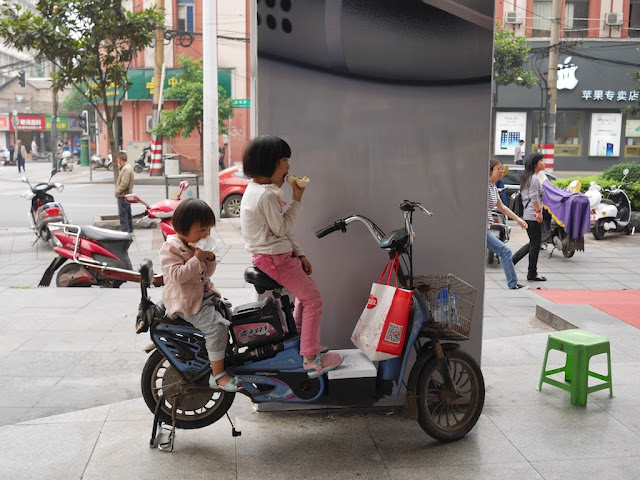 two girl eating while sitting on a parked electric bike in Changsha