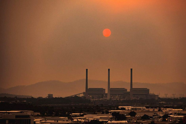 The sun, silhouetted by smoke haze from bushfires, looms over Gladstone, Australia, on 30 November 2018. Photo: Wezley Pitt / ABC