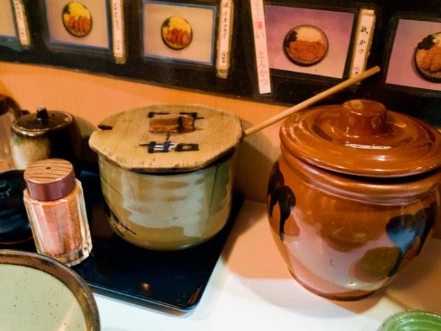 店内のカウンター上。甘口と辛口のソースの壺がある。