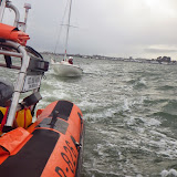 Poole lifeboat, having righted a capsized dinghy, tows it back to the shore with one crew member onboard to Shore Road - 26 April 2014 Photo: RNLI Poole