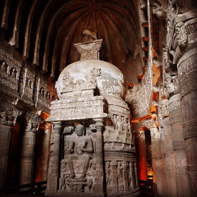 A stupa inside a cave at Ellora, with carved columns to either side and a vaulted roof above.
