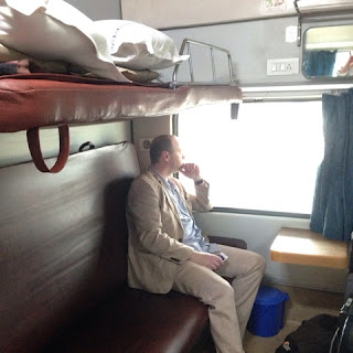 A man in a two-bunk sleeper carriage.