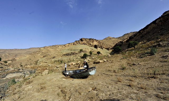 Yemeni men inspect an abandoned boat at a drought-affected dam on the outskirts of Sana'a. Yemen is one of the most water-scarce countries in the world. Photo: Yahya Arhab / EPA