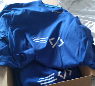 Bok of blue t-shirts with the Rapid XAML logo