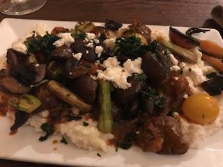 Kjøtt og grønnsaker blandet sammen på en seng av rotmos.