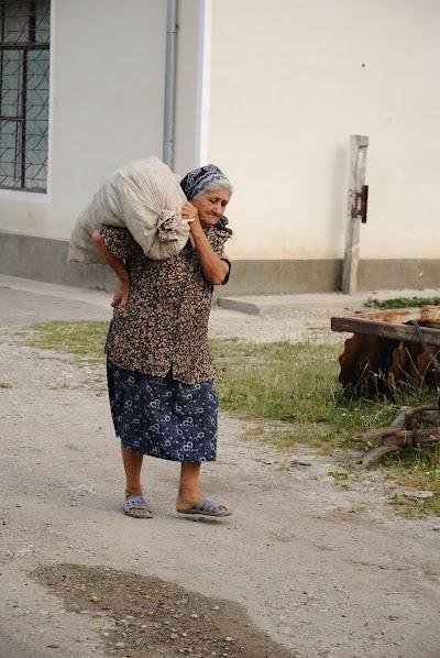 Eine alte Frau trägt einen schweren Sack