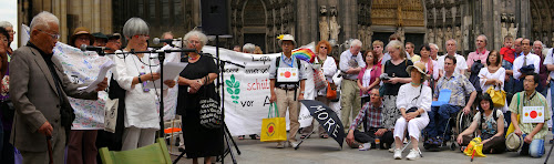 Menschen, stehend, sitzend, knieend, vor dem Dom mit Transparenten und Plakaten.