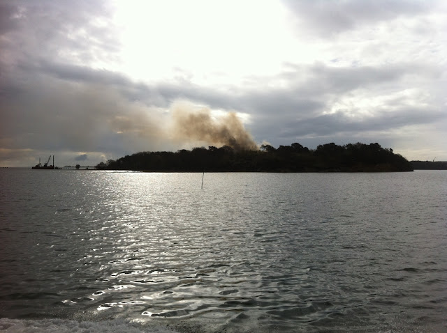 20 April 2012 - Smoke rising from the four-storey building at 0855 on Green Island as Poole's inshore lifeboat heads to the scene to provide back-up for medical evacuation of firefighters if required. Photo: RNLI/Poole Lifeboat Station Richard Skerman