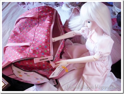 A ball jointed doll checking the size of a cute bag.
