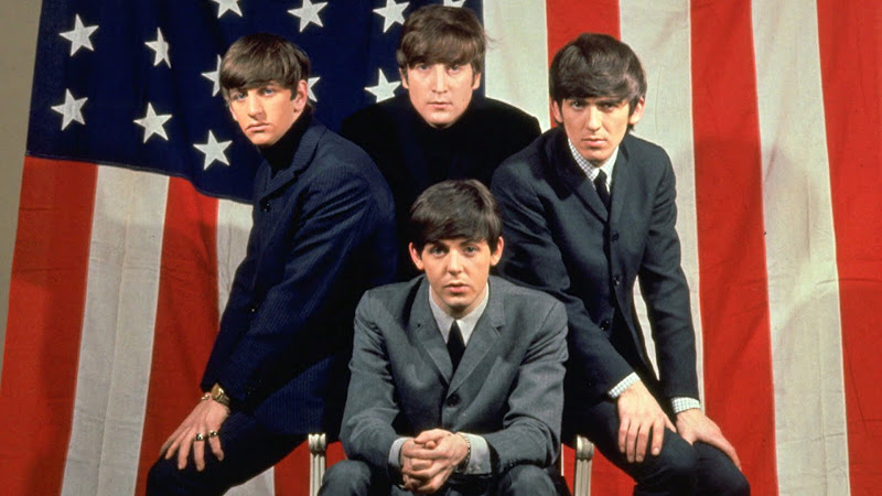 Color image of British rock band The Beatles in front of an American Flag