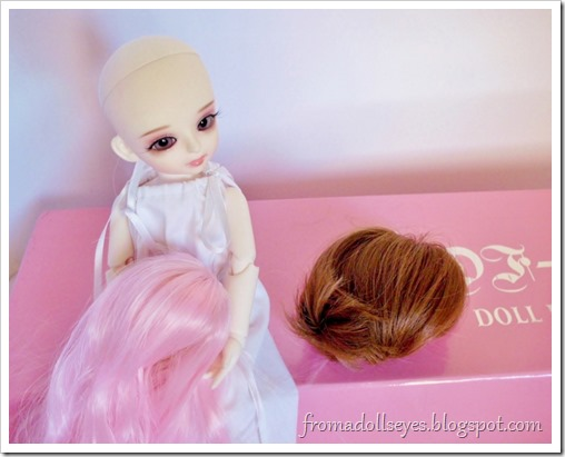 A ball jointed doll choosing a wig.