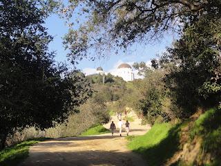 En bred sti med trær hengende over. 3 mennesker går på stien. I bakgrunnen skimtes en hvit bygning med grått kuppelformet tak.
