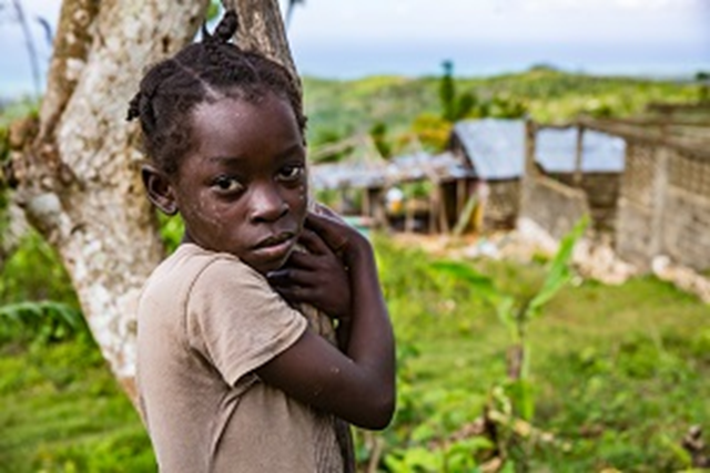 A child stands for a photograph near the destroyed École Mixtes Pierre Louis Marie in Dame-Marie, Haiti, after Hurricane Matthew. Photo: UNICEF / Bradley
